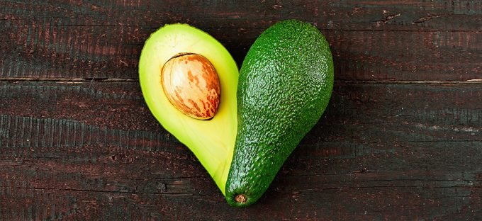 Avocado in heart shape on wooden table
