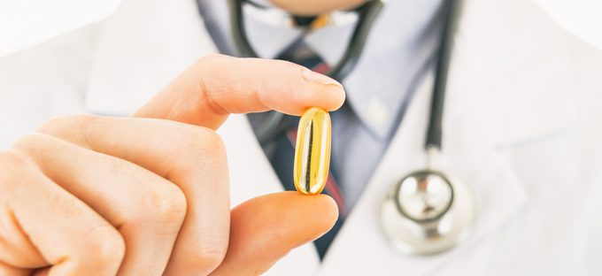 Doctor holding a fish oil pill