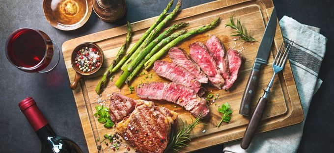 Rib eye steak medium rare on a chutting board with asparagus