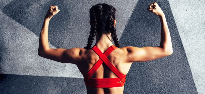 Woman flexing back muscles against a grey wall wearing red sports top