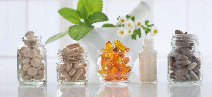 Glass bottles filled with various supplement capsules on a white counter top