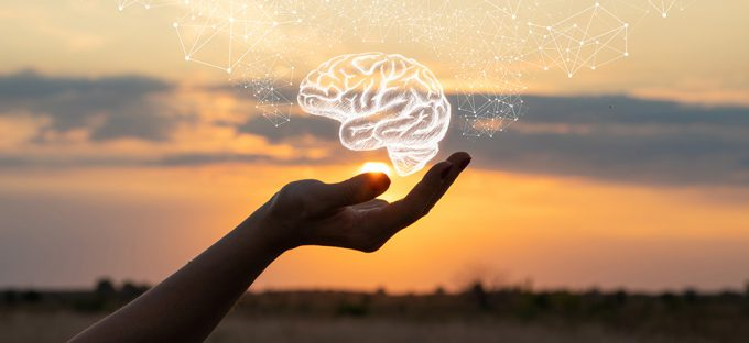 Hand holding a brain drawing against the sun and sky