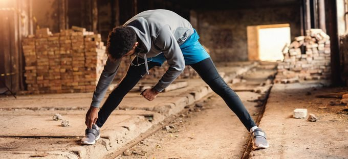 Man in running shoe stretching his hamstring in an abandoned building