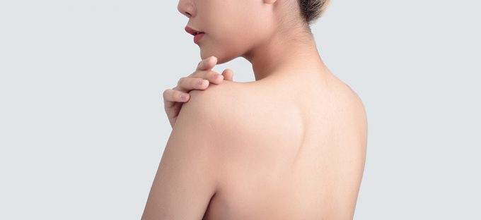 Woman's back on light colored backdrop hand on shoulder